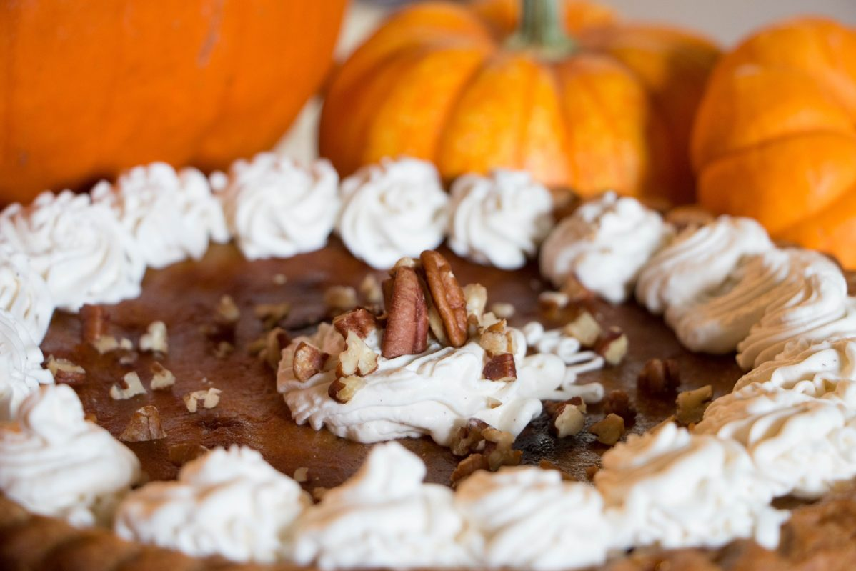 Picture of a pie surrounded by pumpkins
