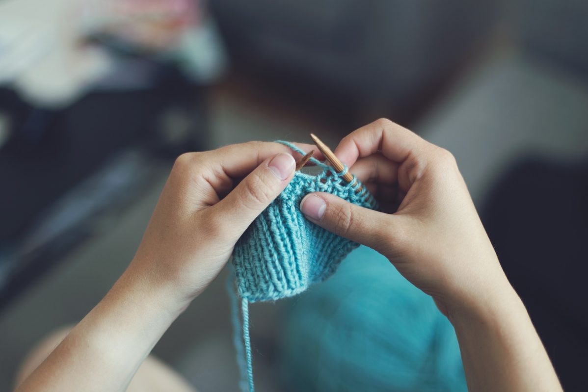 Picture of hands knitting a piece of fabric out of blue yarn