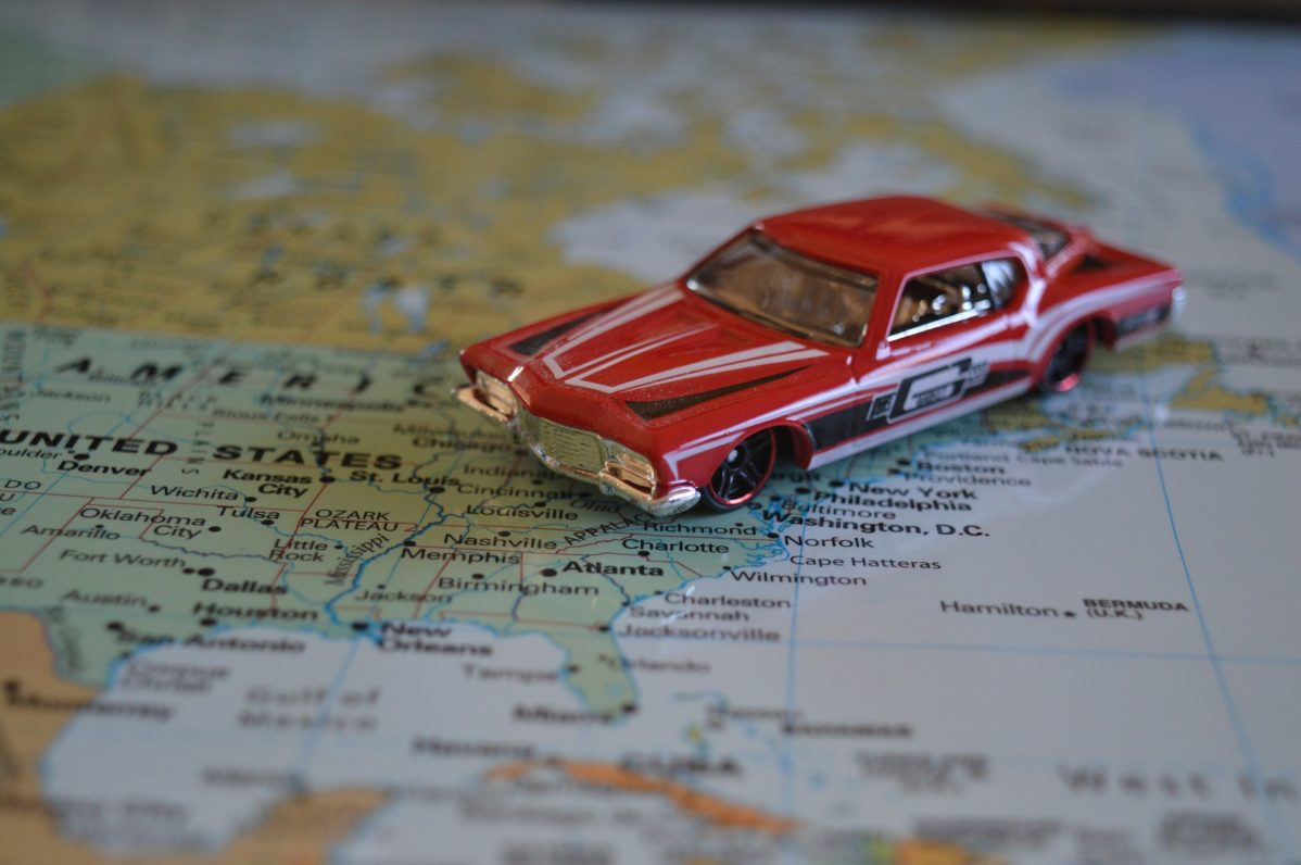 Red toy car on top of a map of the United States